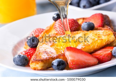 french toasts with fresh berries and pouring honey