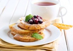 French toasts with icing sugar and berries, cup of tea