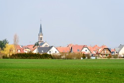 French village with beautiful houses, tall church  and green agricultural field