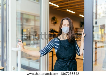 French woman in protective mask open door of the shop for welcome the customer in to the coffee shop, small business owner and startup with cafe shop, installing open and close concept