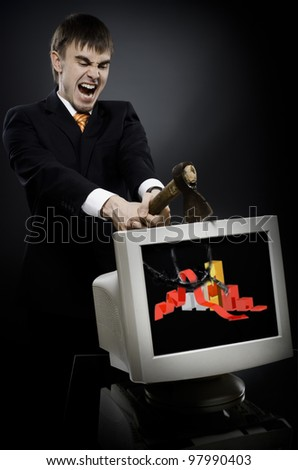 frenzy businessman chop-down old monitor on dark grey background, concept economics  crisis