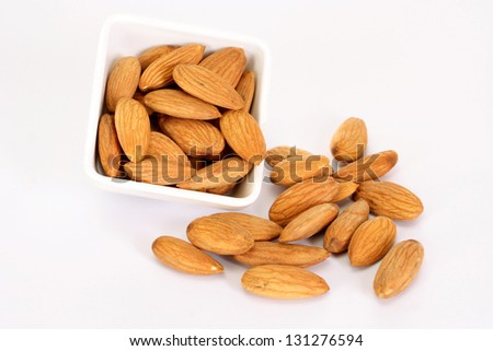 Fresh almonds spill out of bowl