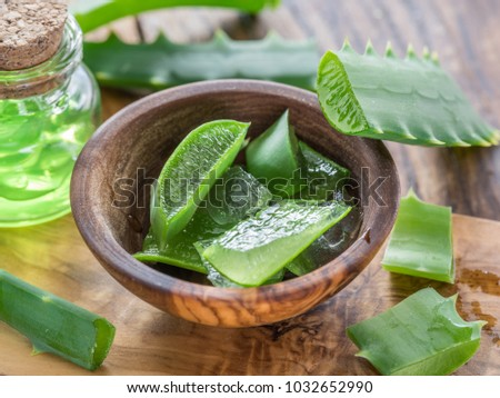 Fresh aloe leaves and aloe gel in the cosmetic jar on wooden table. Stockfoto ©