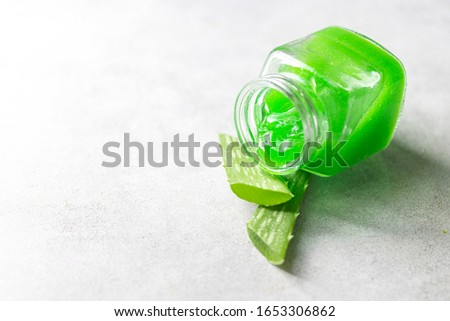 Fresh aloe vera gel in a glass jar with aloe on a light background. Selective focus,copy space for text.
