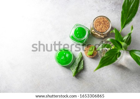 Fresh aloe vera gel in a glass jar with aloe on a light background. Selective focus, copy space for text. Top view.