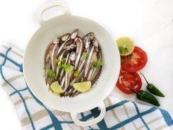 Fresh Anchovy Fish decorated with herbs and vegetables on a white background.Selective focus.