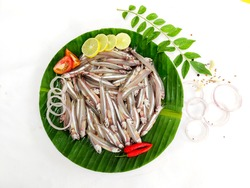 Fresh Anchovy Fish Decorated with Tomatoes Slice, Lemon Slice, Red chili and curry Leaves on a Banana leaf. White Background.