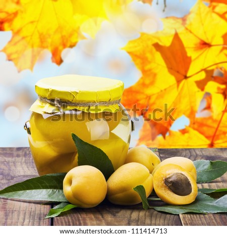 fresh and canned apricot on a background of autumn leaves