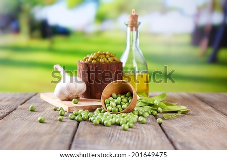 Fresh  and canned peas in bowl and glass jar on napkin, on wooden table, on bright background