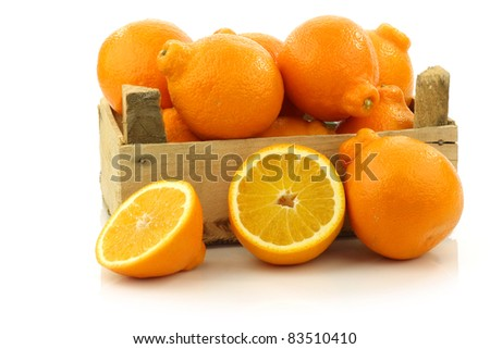 fresh and colorful  Minneola tangelo fruit and a cut one in a wooden crate on a white background