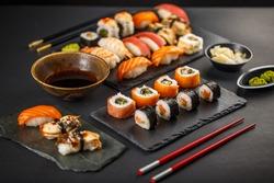 Fresh and delicious sushi set on black slate