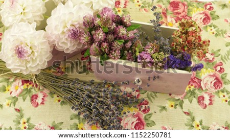 Fresh and dry flowers on the  fabric with floral pattern, floral arrangement #1152250781