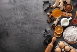 Fresh and healthy ingredients for gingerbread cookies on a dark textured background. Cooking dough for gingerbread cookies. Christmas background for baking, top-down view, copy space.
