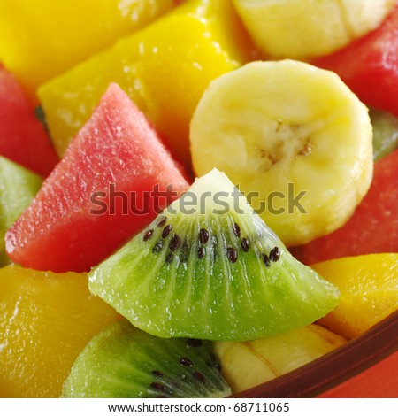 Fresh and healthy tropical fruit salad out of kiwi, mango, banana and watermelon pieces in an orange bowl (Selective Focus, Focus on the kiwi slice)