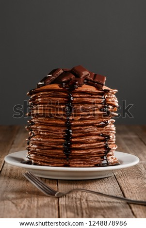 Fresh and hot pancakes with melting chocolate on top of the stack. Mouthwatering picture of a tasty homemade dessert.