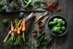 Fresh and organic local produced of various raw vegetables, looks so colourful on the wooden rustic table. moody light.