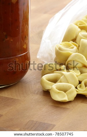 fresh and raw wholegrain tortellini  pasta with tomato sauce jar , the perfect ingredients to make an easy and fast delicious meal.