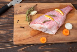 Fresh and ready to cook raw pink Perch fish with ingredients like lemon and carrot on a wooden pad, selective focus.
