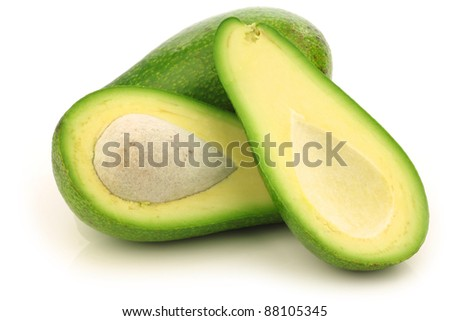 fresh and ripe avocado and a cut one on a white background