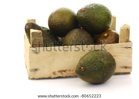 fresh and ripe avocado's in a wooden crate on a white background
