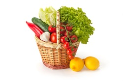 Fresh and ripe vegetables and fruit arranged in a basket isolated on white. Healthy vegan food.