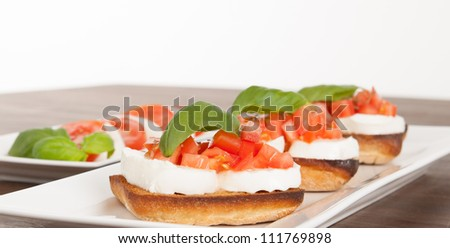 Fresh and tasty bruschetta served on a white plate