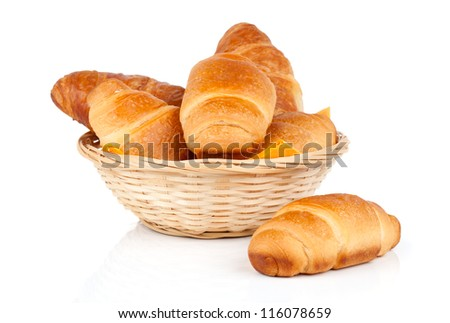 Fresh and tasty croissant in a straw basket, isolated on the white background - stock photo