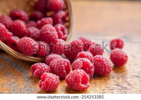 Fresh and tasty looking raspberries on a wooden table