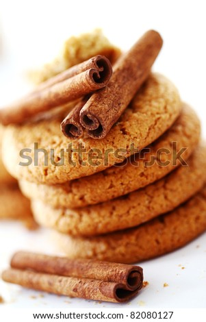 Fresh and tasty oat biscuits with cinnamon sticks on white background