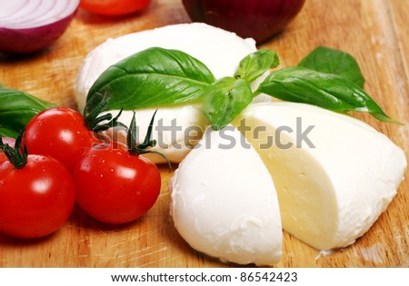 Fresh and tasty tomatoes, basil and mozzarella on wooden board