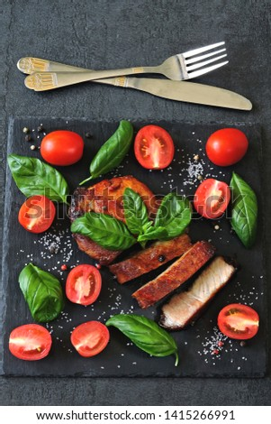 Fresh appetizing meat steak on a board with tomatoes and basil. Keto diet. Paleo diet. Pegan Diet. #1415266991