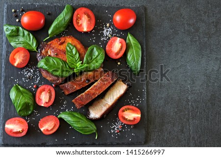 Fresh appetizing meat steak on a board with tomatoes and basil. Keto diet. Paleo diet. Pegan Diet. #1415266997