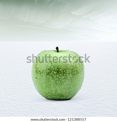 Fresh apple concept with frozen granny smith in snow landscape