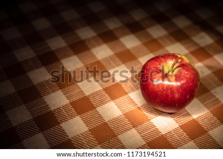 Fresh apple on a red and white checked cloth