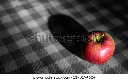 Fresh apple on a red and white checked cloth. black and white background
