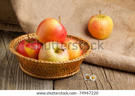 Fresh apples in basket on old wooden table and sacking as background