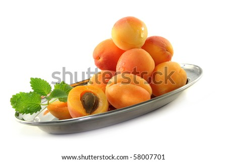 fresh apricots and lemon balm on white background