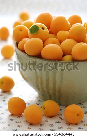 fresh apricots in a big green bowl, close up, full page, blurred background #634864445
