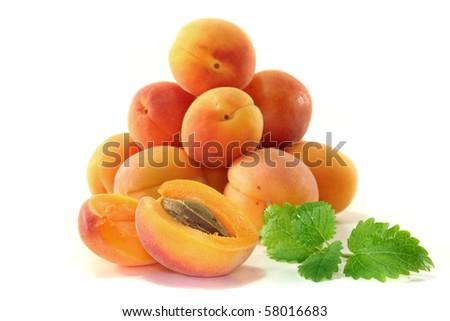 fresh apricots with lemon balm on white background