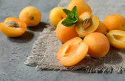 fresh apricots with mint on a gray background, whole and half orange berries