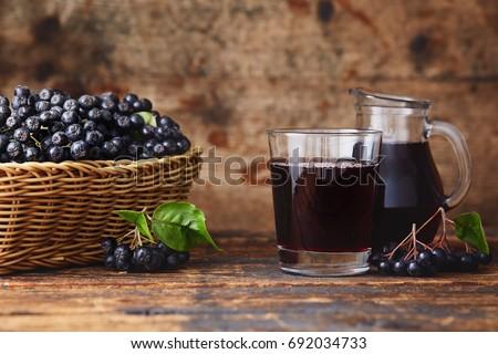 Fresh aronia berries and aronia berry juice in glasses