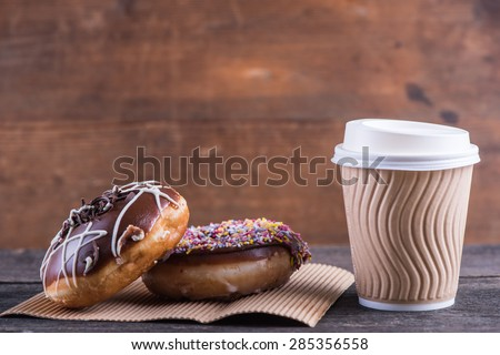 fresh artisan donuts and take away coffee, wooden background with copy space