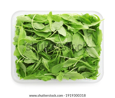 Fresh arugula in plastic container isolated on white, top view Сток-фото ©