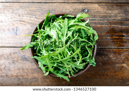 fresh arugula salad in a clay plate on the table. space for text Сток-фото ©