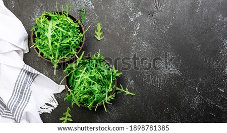 Fresh arugula salad leaves in two clay bowls on black rustic background with copy space for your design. Healthy diet food concept. Restaurant menu, cooking blog template. Minimalism style composition ストックフォト ©