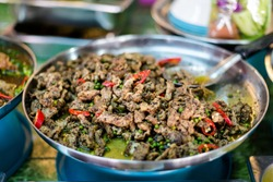Fresh asian spicy green pepper corns and chilli pork slices on local market in Krabi town. Traditional thai cuisine made of fresh ingredients.