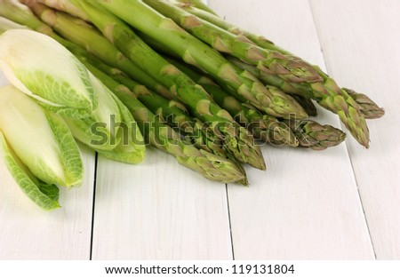 Fresh asparagus and chicory on white wooden table background