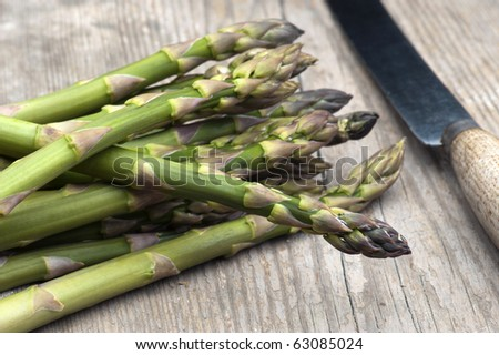 Fresh Asparagus Laid Out On A Rustic Kitchen Table With A Vegetable Knife