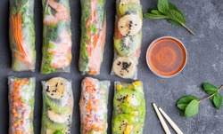 Fresh assorted Asian spring rolls with shrimps, vegetables, fruit, rustic concrete background