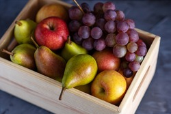 fresh assorted fruits in a wooden box, pears, apples, grapes, close-up
